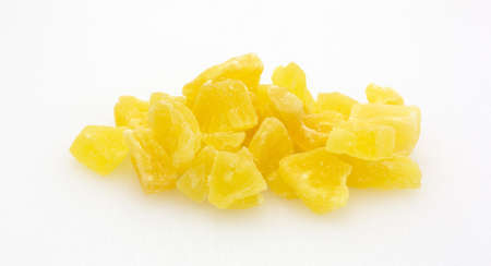 chunks: A serving of dried sugared pineapple chunks on a plastic cutting board. Stock Photo