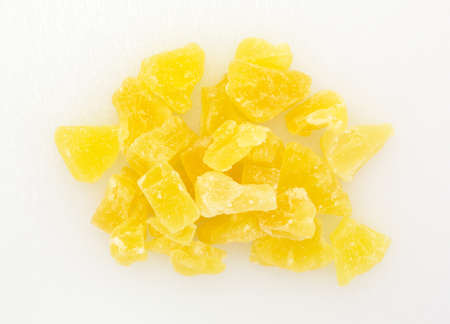 chunks: Top view of a serving of dried sugared pineapple chunks on a plastic cutting board.