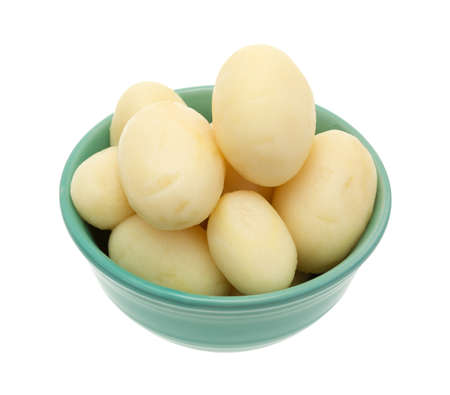 previously: A small bowl filled with canned whole white potatoes isolated on a white background.
