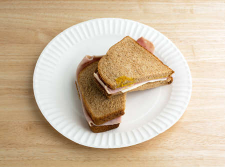 luz natural: A ham and cheese sandwich that has been cut in half on a white paper plate atop a wood table top illuminated with natural light.