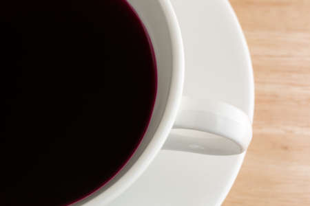 beet juice: A close view of beet juice in a white coffee cup and saucer atop a wood table top. Stock Photo