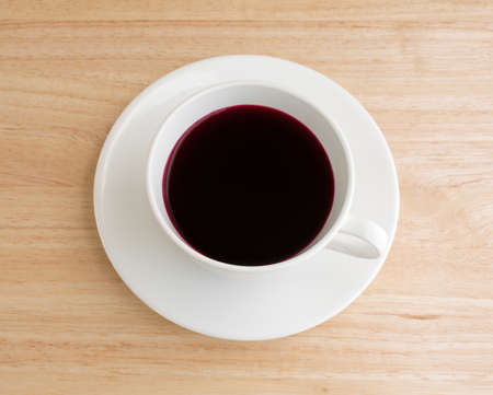 beet juice: Beet juice in a white coffee cup and saucer atop a wood table top illuminated with natural light.