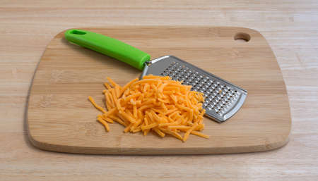 cheddar cheese: A portion of cheddar cheese that has been grated with a cheese grater atop a wood cutting board and counter top.