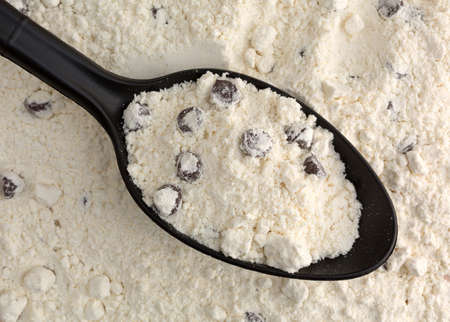Top view of dry chocolate chip cookie mix in a black spoon on top of more mixture illuminated with natural light. 版權商用圖片