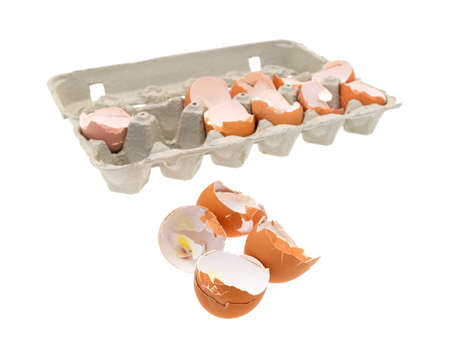 A group of broken and used eggs in the foreground with the remainder in a cardboard carton in the background.