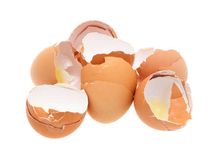 broken: A group of broken and used brown eggshells isolated on a white background.