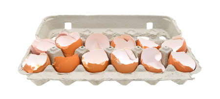 dozen: A dozen broken eggshells in an opened cardboard container on a white background. Stock Photo