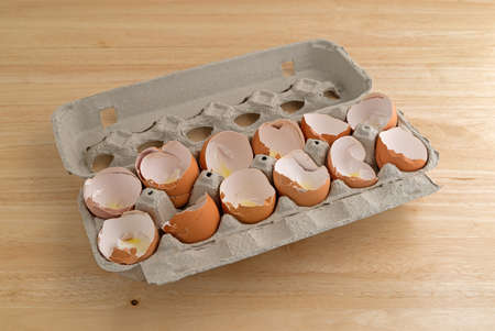 dozen: A dozen broken eggshells in an opened cardboard container on a wood counter top illuminated with natural light.