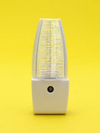 automatically: A new generic LED night light that turns on automatically in darkness on a yellow background.