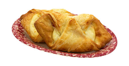 serving dish: Several cheese danish pastries on an old mottled red serving dish isolated on a white background.