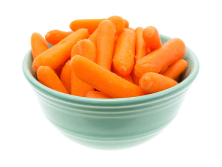 A large serving of organic small baby carrots in a green bowl isolated on a white background. Banco de Imagens