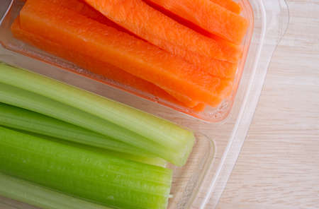 Several freshly cut carrot sticks and celery sticks in a translucent plastic tray atop a wood table top illuminated with natural light. Banque d'images