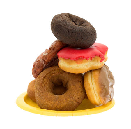 fritter: A yellow paper plate with a stack of assorted donuts and iced cherry fritter on a white background. Stock Photo