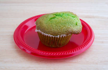 tabletop: A freshly baked pistachio breakfast muffin on a red plastic plate atop a wood tabletop illuminated with natural light.