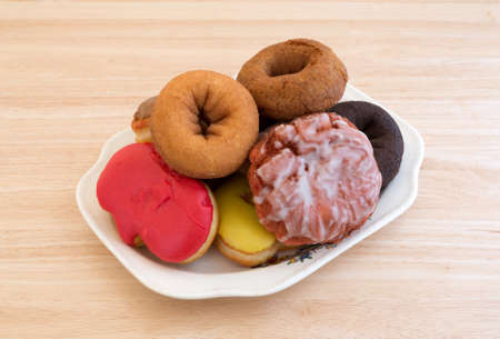 fritter: An old platter with several donuts and an iced cherry fritter atop a wood table top illuminated with natural light.