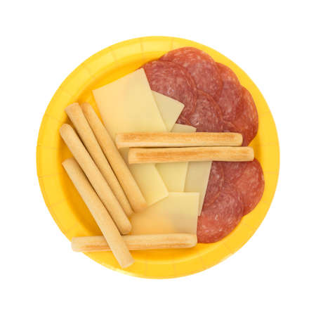 gressins: Top view of a yellow paper plate with of slices of provolone cheese and genoa salami plus breadsticks isolated on a white background. Banque d'images