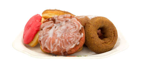 An old platter with several donuts and an iced cherry fritter isolated on a white background. Zdjęcie Seryjne