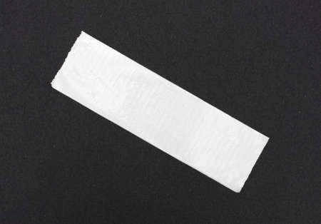 masking tape: A short length of white duct tape stuck to black craft paper.