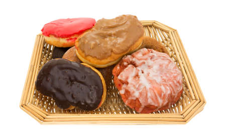 fritter: An old wicker basket filled with assorted donuts and iced cherry fritter on a white background.