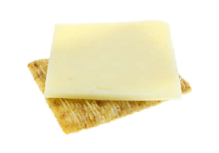 A slice of cheddar cheese upon a whole wheat cracker isolated on a white background. Stock fotó