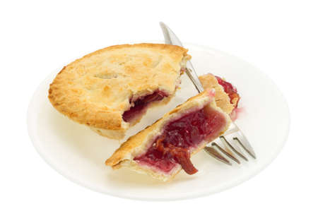 cherry pie: A small cherry pie in pieces on a plate with fork isolated on a white background.