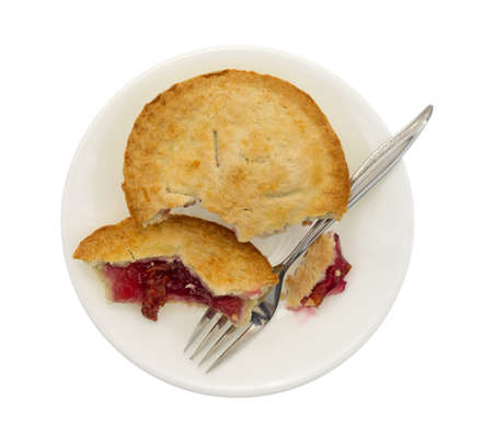 cherry pie: Top view of a small cherry pie in pieces on a plate with fork isolated on a white background.