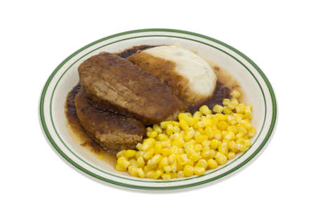 pastel de carne: A microwaved meatloaf with gravy plus mashed potatoes and corn TV dinner on a plate isolated on a white background.