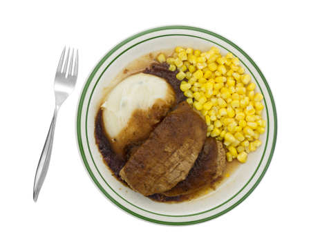 Top view of a microwaved meatloaf with gravy plus mashed potatoes and corn TV dinner on a plate with fork to the side isolated on a white background.