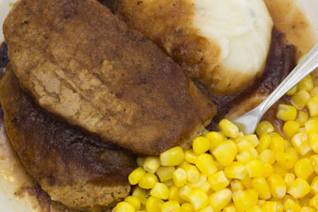 Close view of a microwaved meatloaf with gravy plus mashed potatoes and corn TV dinner with a fork inserted into the meal. Stock Photo