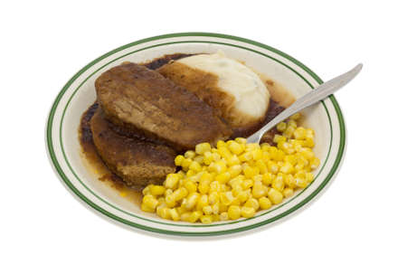 A microwaved meatloaf with gravy plus mashed potatoes and corn TV dinner on a plate plus a fork inserted into the food isolated on a white background.