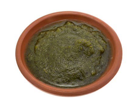 A bowl of pesto isolated on a white background.