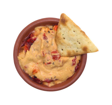 red peppers: A small bowl with a serving of hummus with red peppers plus a single pita snack cracker inserted into the dip isolated on a white background. Stock Photo