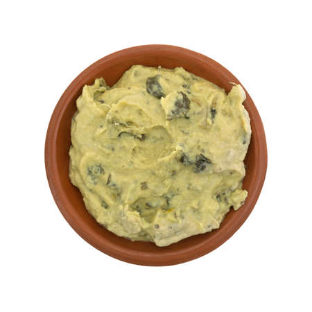 olive green: Top view of a portion of freshly made packaged spinach hommus in a small bowl isolated on a white background.