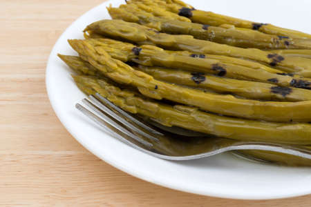 sunflower oil: Close view of a serving of grilled asparagus drenched in sunflower oil on a white plate with a fork atop a wood table top illuminated with natural light. Stock Photo