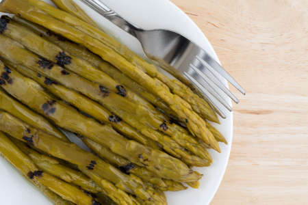 sunflower oil: Top close view of a serving of grilled asparagus drenched in sunflower oil on a white plate with a fork atop a wood table top illuminated with natural light.