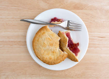 tines: Top view of a small cherry pie in pieces on a plate with a fork atop a wood table top illuminated with natural light. Stock Photo