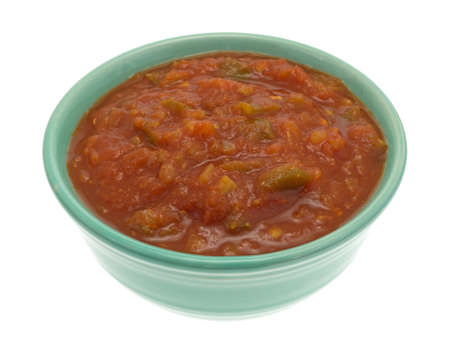 tex mex: Side view of a bowl of chunky spicy salsa sauce isolated on a white background.