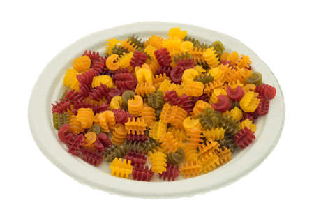 Side view of gluten free corn vegetable radiatore pasta on a paper plate isolated on a white background. 版權商用圖片
