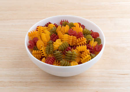 free dish: A portion of gluten free corn vegetable radiatore pasta in a white bowl on a wood table top illuminated with natural light. Stock Photo