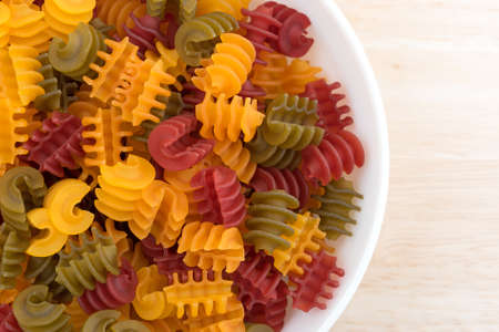 free dish: Top close view of a portion of gluten free corn vegetable radiatore pasta in a white bowl on a wood table top illuminated with natural light. Stock Photo