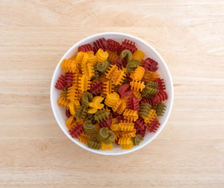 free dish: Top view of a portion of gluten free corn vegetable radiatore pasta in a white bowl on a wood table top illuminated with natural light. Stock Photo