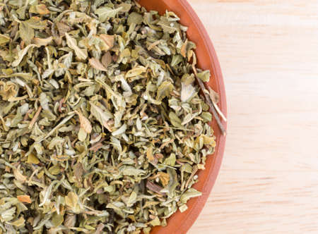 damiana: Top close view of a portion of damiana leaf in a small bowl on a wood counter top. Stock Photo