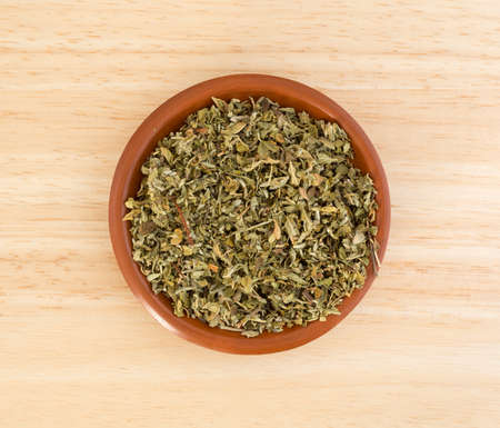 holistic view: Top view of a portion of damiana leaf in a small bowl on a wood counter top.