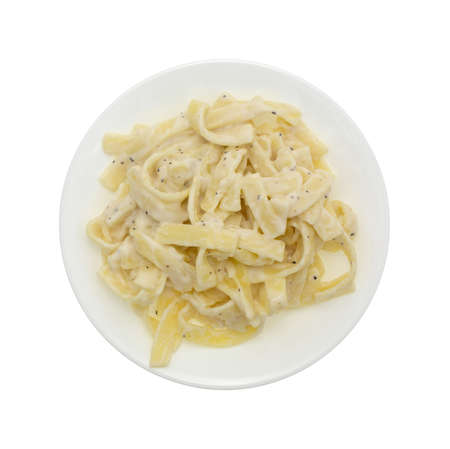 Top view of a microwaved fettuccine alfredo TV dinner on a plate with a isolated on a white background.