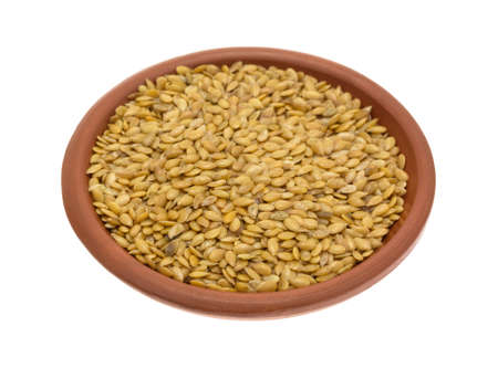 flaxseed: Side view of a bowl of organic golden flaxseed isolated on a white background.