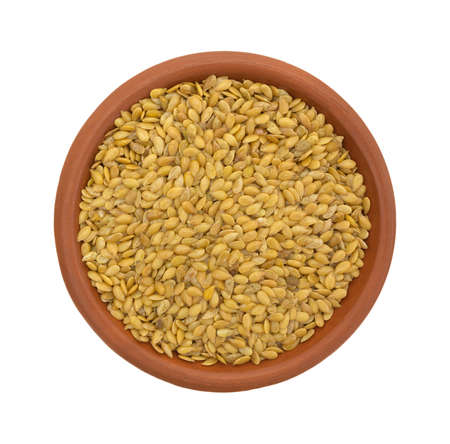 flaxseed: Top view of a bowl of organic golden flaxseed isolated on a white background. Stock Photo