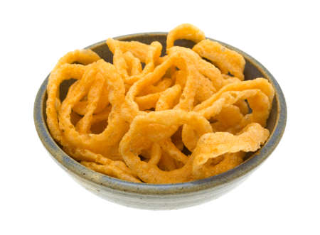 stoneware: Side view of a large serving of crunchy onion rings in an old stoneware bowl isolated on a white background.