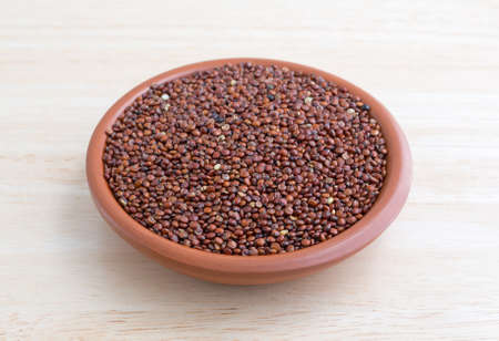 red quinoa: A portion of red quinoa in a small bowl on a wood table top illuminated with natural light. Stock Photo