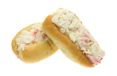 Two small surimi crab meat made into a salad with mayonnaise in small sub rolls isolated on a white background.