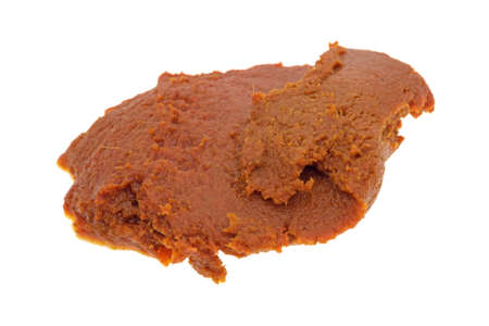 blob: Side view of a blob of red curry paste isolated on a white background.
